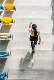 Elevated view of sportswoman running on stadium stairs. Young girl running concept Royalty Free Stock Photos
