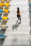 Elevated view of sportswoman running on stadium stairs. Young girl running concept Stock Photography