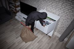 Thief Stealing File From Shelf. Elevated View Of Thief With Crowbar And Sack Stealing File From Shelf stock image