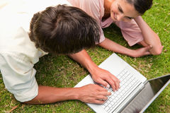 Elevated view of two friends using a laptop together. Elevated view of two friends smiling while using a laptop together as they lie down on the grass Royalty Free Stock Image