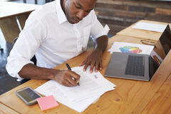 Elevated view of young black man working at office desk Stock Images