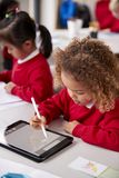 Elevated view of young schoolgirl wearing school uniform sitting at desk in an infant school classroom using a tablet computer and. Stylus, close up, vertical stock photos