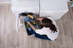 Elevated View Of A Woman Loading Clothes In Washing Machine royalty free stock image