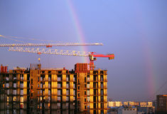 Elevating crane. The elevating crane of construction on a background of the dark blue sky and a rainbow Royalty Free Stock Images
