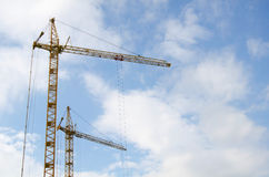 Elevating crane against the cloudy sky Royalty Free Stock Image
