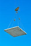 Elevating crane lifting a concrete plate Stock Photo