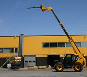 Elevating crane near a warehouse Royalty Free Stock Images