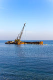 The elevating crane unloads stones at sea. Stock Photo
