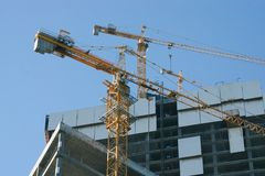Elevating cranes on a construction site Royalty Free Stock Image