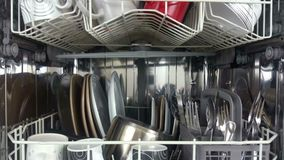 Elevating shot of a dish washer loaded with crockery and cutlery stock footage