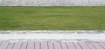 Elevation of the timber terrace, green grass lawn and low height. Stone wall texture and pattern Royalty Free Stock Photography