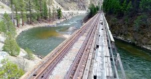 Aerial view of a train track bridge that leads over a bridge. Elevation view of a train trestle from the river side stock video footage