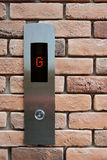 Elevator button down floor G on brick texture background. Royalty Free Stock Photos