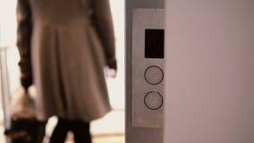 Elevator come to floor, door opens, woman comes in the elevator, press the button and door closed. 4K