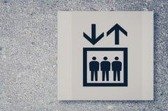 Elevator- eller hisssymbol på betongväggen Arkivbilder