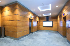 Elevator hall in business center. 3 lift doors, TV set on a wall. Wooden walls, Granite floor Stock Images