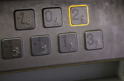 Elevator keypad. Button pressed to go to the second floor. Buttons all have brail translations Stock Images