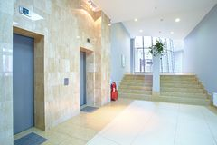 The elevator lift hall and a stairway. Are located in the business center in the modern building in a light colors Royalty Free Stock Photography