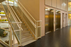 Elevator staircase in a modern building. An elevator and glass staircase in a modern metropolitan building Royalty Free Stock Image