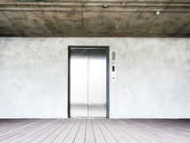 Elevator on wooden floor and concrete wall Royalty Free Stock Images