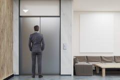 Elevatore aspettante dell'uomo nell'ingresso della società Fotografia Stock
