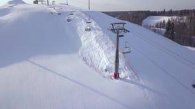 Elevatore dello sci per gli sciatori e gli snowboarders del trasporto sulla montagna della neve nella vista aerea della località  archivi video