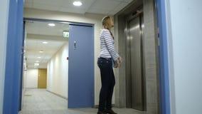 Elevatore di chiamata ed aspettante della giovane donna archivi video