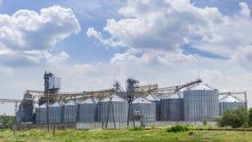 Elevatore di grano con il silos d'acciaio sui precedenti del cielo Immagine Stock Libera da Diritti
