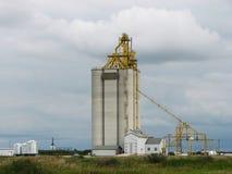 Elevatore di grano concreto con il cielo nuvoloso sulla prateria Immagini Stock Libere da Diritti