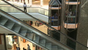 Elevators and escalators ascending within mall. A view or scene of Shopping stock footage