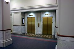 Elevators in lobby. Two brass elevators sit side by side in this marble covered lobby with high ceilings and blank walls Royalty Free Stock Image