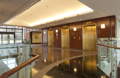 Elevators in office building. Elevators in brass and mahogany located in modern office building Stock Photos