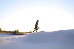 Elevazione dei musulmani maschii alla cima della duna di sabbia sopra la sabbia bianca dentro Fotografia Stock Libera da Diritti