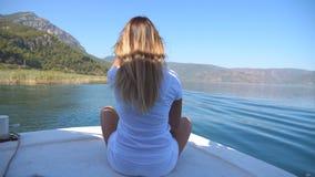 Eleve a opinião traseira a moça que senta-se na curva do barco e que olha à paisagem bonita da natureza no dia ensolarado Mulher  filme