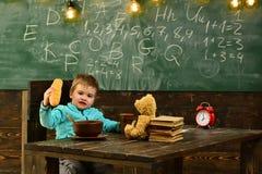 Eleven äter mat på trätabellen Den lilla eleven tycker om lunchavbrottet i klassrum Skolameny för elev Idagen är eleven royaltyfri foto