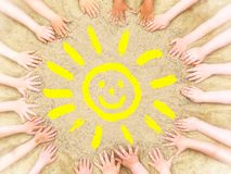 Child hands frame a yellow smiling sun royalty free stock photo