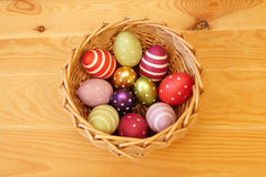 Eggs in Easter Basket. Eleven colored easter eggs in the basket on the wooden background Stock Photos