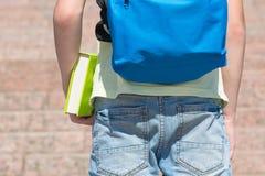 Eleven med en ryggsäck på hans baksida rymmer en bok i hans handnärbildsikt bakifrån Arkivfoton