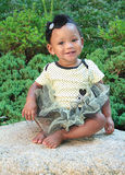 An Eleven Month Old Girl on a Rock. With a tutu on. She is smiling and very happy stock photography