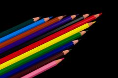 Eleven coloured pencils in shape of an Arrow Isolated on a black back ground Royalty Free Stock Photos