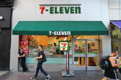 7-Eleven New York. NEW YORK, USA - JULY 3, 2013: People walk past 7-Eleven convenience store in New York. 7-Eleven is world's largest operator, franchisor and royalty free stock photos
