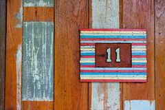 11, eleven, numeral of wood combined with yellow insert, plate a Stock Photography