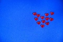Eleven red glass hearts on a blue background. Valentine`s Day royalty free stock images