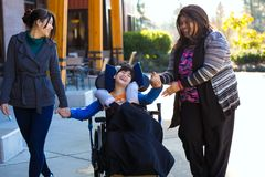 Disabled boy in wheelchair holding hands with caregivers on walk Stock Photo