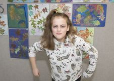 Eleven year old girl in humorous mean girl pose. Pictured is an eleven year old girl in a humorous mean girl pose.  She scowling humorously and leaning forward Stock Image