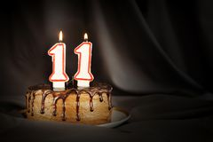 Eleven years anniversary. Birthday chocolate cake with white burning candles in the form of number Eleven. Dark background with black cloth stock image