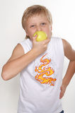 Eleven years old boy with an apple. An eleven-year boy eats an apple. On white background Stock Photo