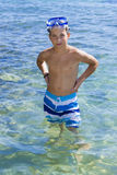 Eleven years old boy sitting on a rock in the sea royalty free stock image