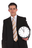 Eleventh hour. A handsome businessman holding a clock that shows the eleventh hour. All on white background Stock Image