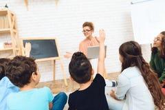 Elever drar händer till frågan för svarslärare` s i exponeringsglas på grundskola för barn mellan 5 och 11 år arkivbild